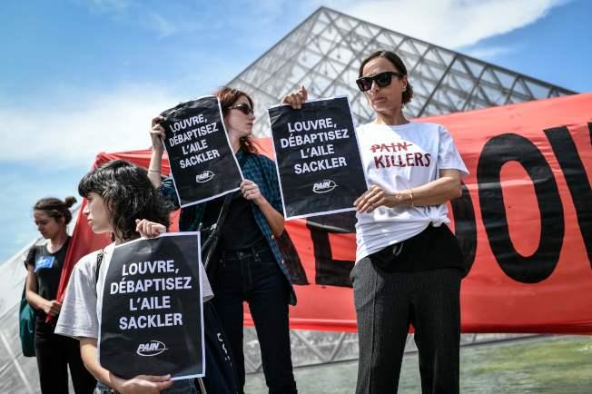 示威者在巴黎羅浮宮博物館前舉牌,要求羅浮宮與售賣類鴉片藥物致富的塞克勒家族畫清界線。(Getty Images)