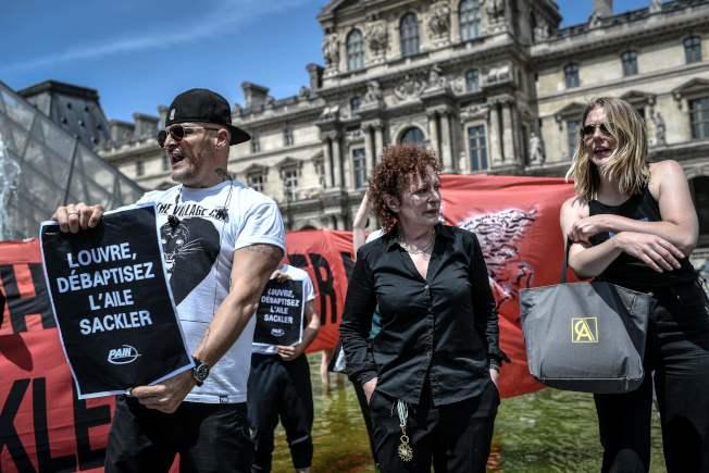 示威者在巴黎羅浮宮博物館舉牌,要求羅浮宮與售賣類鴉片藥物致富的塞克勒家族畫清界線。(Getty Images)