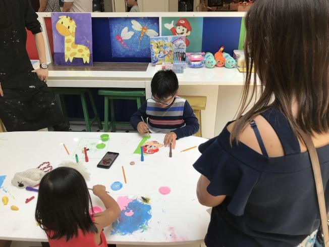 魁北克3歲的女兒和7歲的兒子正在作畫。(記者梁雨辰/攝影)