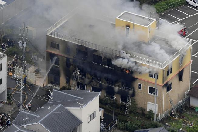 日本京都伏見區「京都動畫」公司18日遭縱火,造成33人慘死,圖為燃燒中的三層樓建物不斷冒出濃煙。(美聯社)