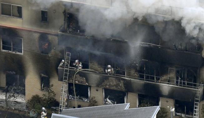 日本京都伏見區「京都動畫」公司18日遭縱火,造成33人慘死,圖為燃燒中的三層樓建物不斷冒出濃煙,消防員冒險搶救。(路透)