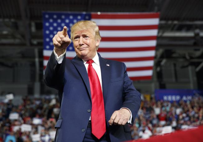 川普總統17日晚間在北卡格林維爾造勢,向群眾打招呼。(美聯社)