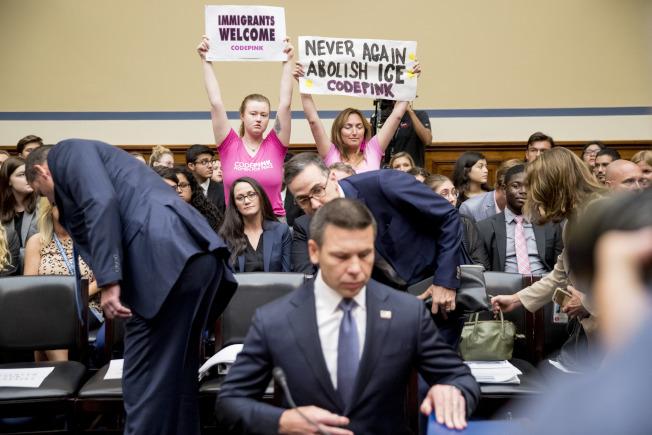 國土安全代理部長麥卡利南(前中)18日在國會時,移民維權人士在後舉牌抗議。(美聯社)