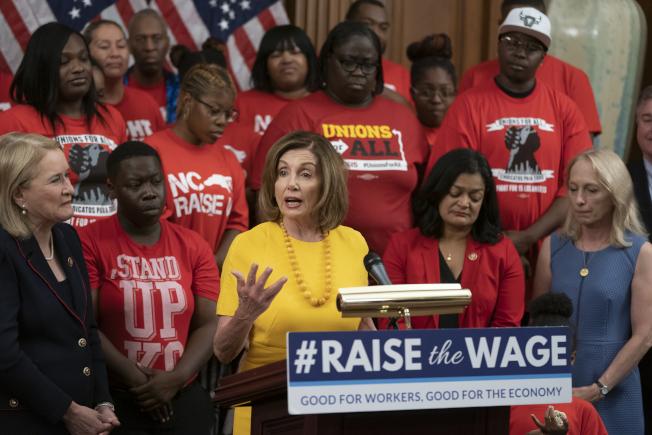 眾院18日通過「提高薪資」法案,未來六年將逐步把聯邦最低時薪提高到15元。圖為法案通過後,波洛西與議員和活動分子出席記者會。(美聯社)