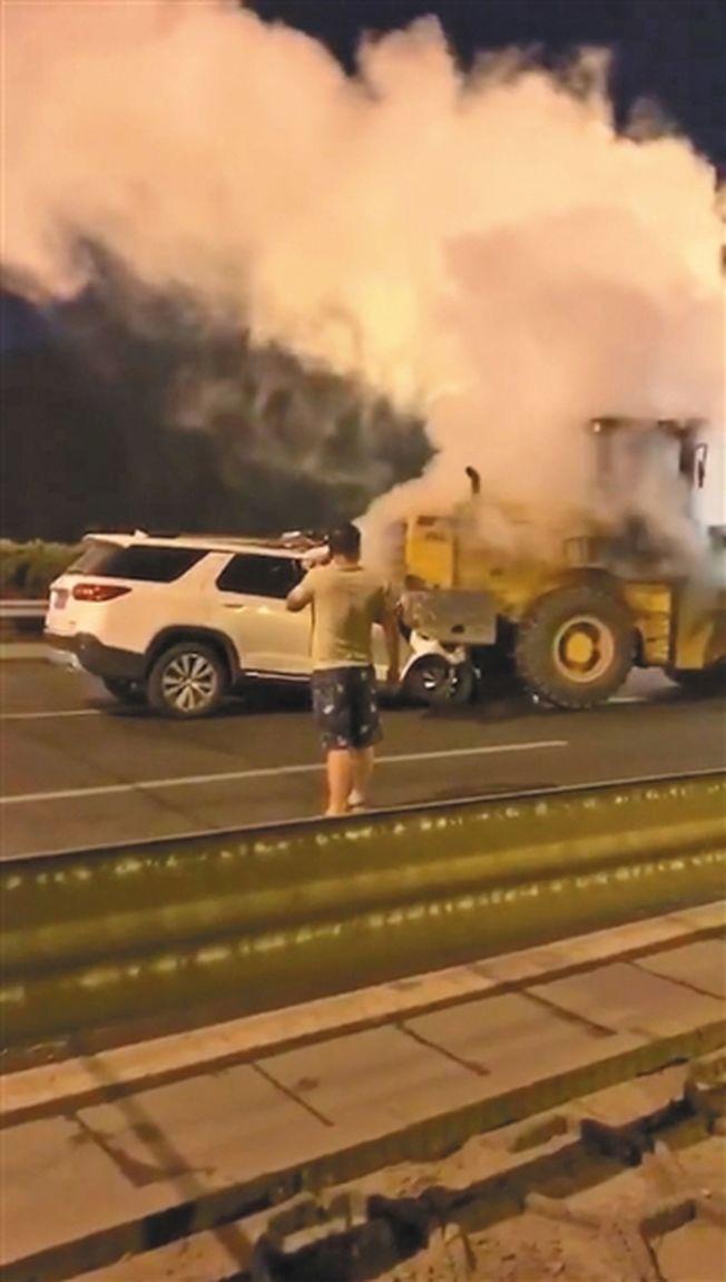 視頻顯示,白車冒起白煙,鏟車駕駛員正在打電話。(取材自新京報)