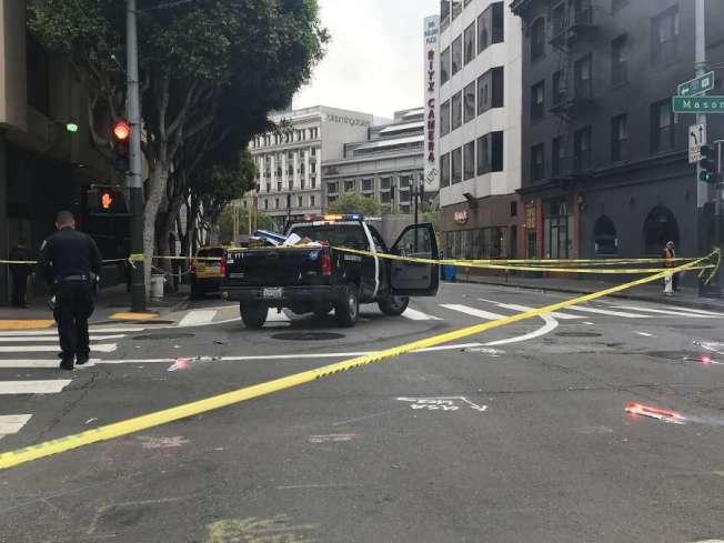 舊金山18日早上,市場街和第5街的路口又發生一起肇事後逃逸的車禍,一名小卡車撞上一名路人,並他拖從數十呎,受害人傷重死亡。圖為車禍現場。(電視新聞截圖)