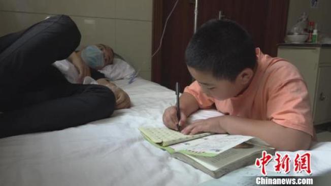 照顧爸爸之餘,路子寬趴在病床上學習功課。(取材自中新網)