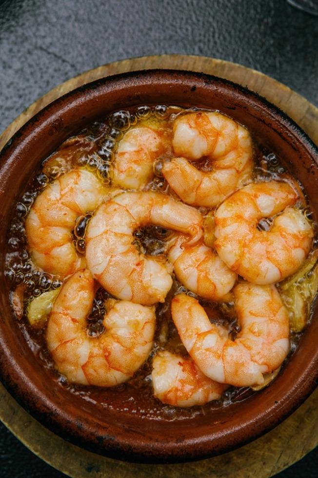 蒜香蝦油是Socarrat Paella Bar的熱門前菜,饕客可搭配麵包一起吃。(取自餐館周官網)