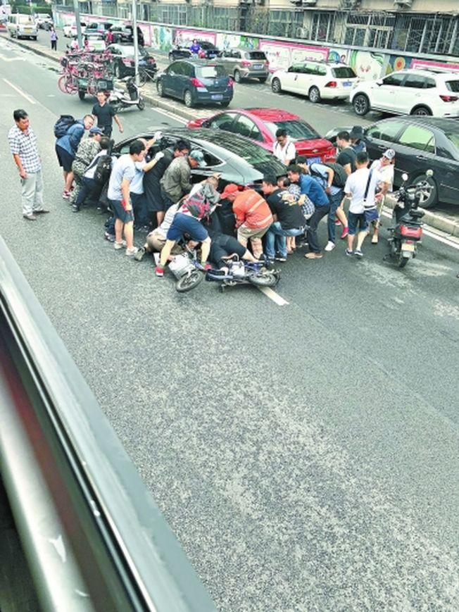 十多公車乘客抬車相助。(取材自北京晚報)