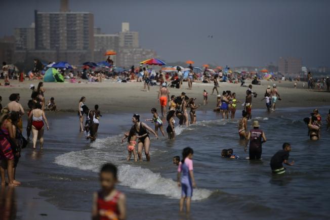紐約周末氣溫將破百。圖為許多民眾在布魯克林的康尼島(Coney Island)海灘玩水。美聯社