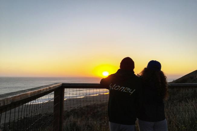 在沙灘觀看日落的小情侶。