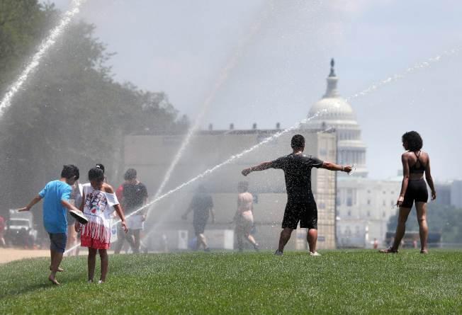 華府國家大草坪打開灑水系統,供民眾驅暑。(Getty Images)
