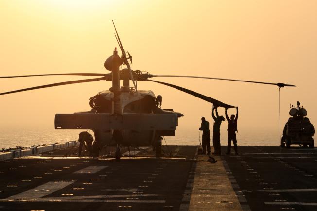 一架海鷹式直升機降落在美國兩棲攻擊艦「拳師號」甲板上,旁邊就是「陸戰隊輕型防空综合系統」,據說就是這套防空系統摧毀伊朗無人機。(路透)
