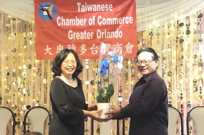 大奧蘭多台灣商會副會長周皇任(右)代表獻花給會長徐國鈴(左),感謝她的傑出領導和辛勞。(林哲光提供)