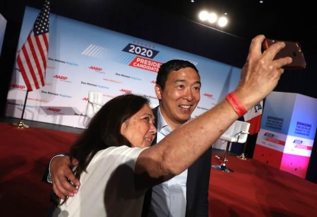 爭取民主黨總統提名的華裔楊安澤,在愛阿華州AARP競選時與選民玩自拍。(Getty Images)