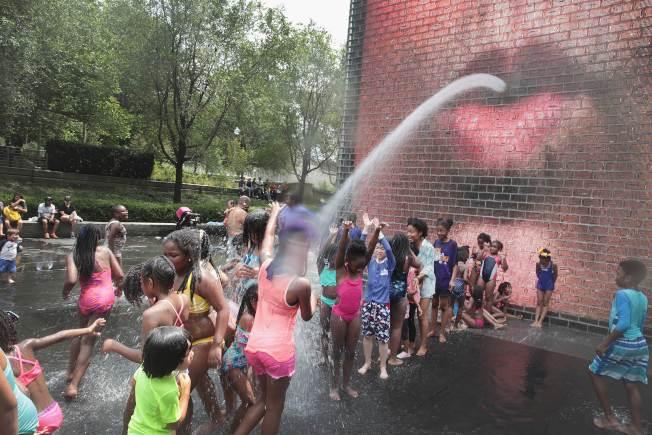 大半個美國在這個周末均籠罩在熱浪下,圖為芝加哥孩童在市區皇冠噴泉戲水驅暑。(Getty Images)