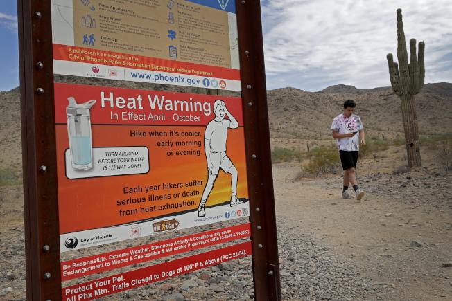 亞利桑納州南山保留區的路邊,豎立警告牌,提醒健行者要注意補充水份。(美聯社)