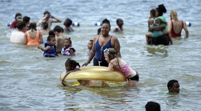大半個美國在這個周末均籠罩在熱浪下,圖為居民在麻州歐諾塔湖戲水驅暑。(美聯社)