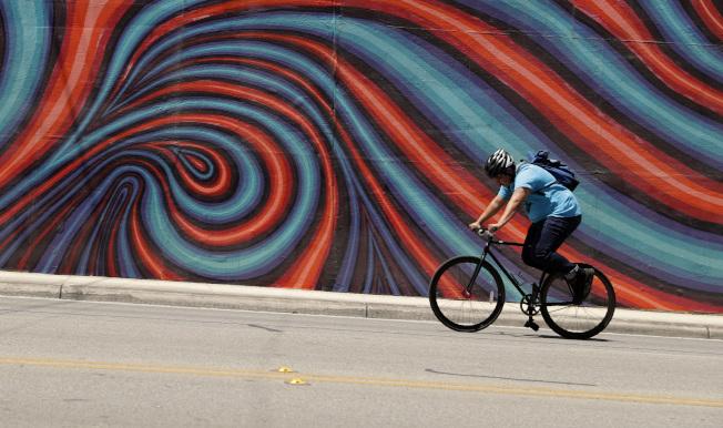 德州聖安東尼奧氣溫接近華氏百度,一名自行車騎士頂者驕陽在市區騎行。(美聯社)