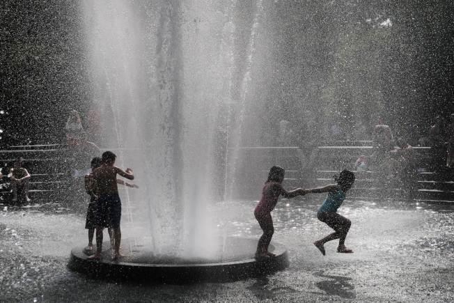 孩童跳進紐約市曼哈頓華盛頓廣場噴泉戲水驅暑。(Getty Images)