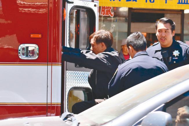 被打至半臉腫脹瘀青的僑領黃宏昶(圖左),等了30分鐘才坐上救護車,被送到醫院治療。(記者李秀蘭/攝影)