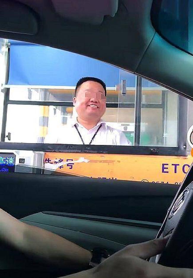 浙江寧波某高速路收費站的男收費員微笑送客,被戲稱「中國版假笑男孩」。 (視頻截圖)