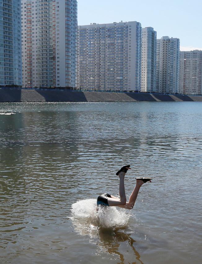 俄羅斯西伯利亞,孩子跳入河中躲熱浪。(路透)