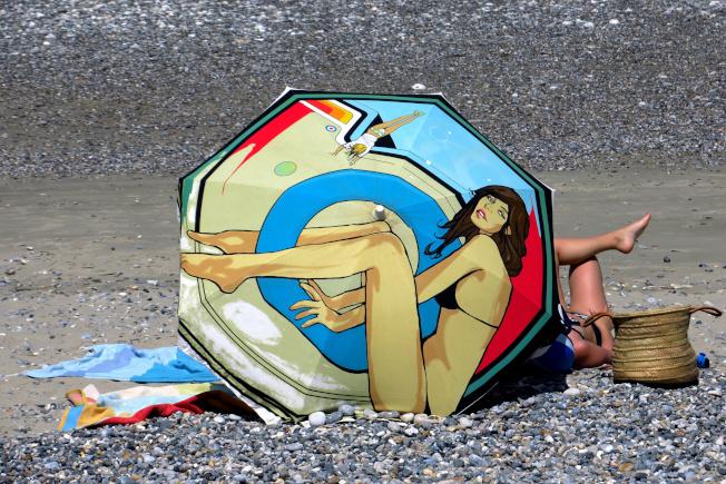 法國,一位女性在海灘上日光浴。(路透)