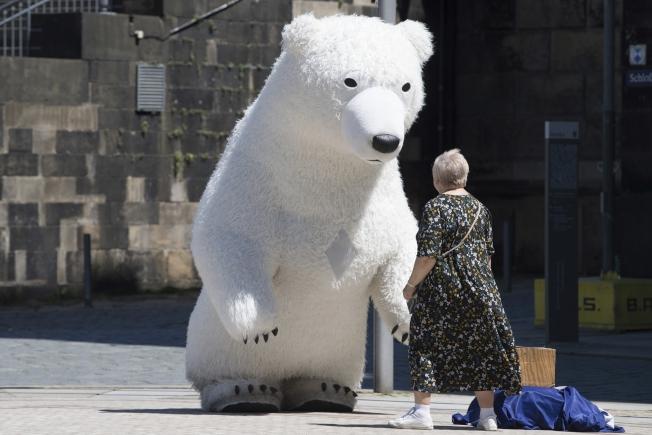 德國一處街頭,表演者打扮成北極熊的模樣。(美聯社)