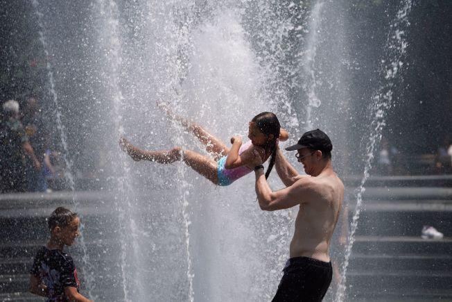 紐約民眾衝進噴泉,把自己淋個溼透。(Getty Images)