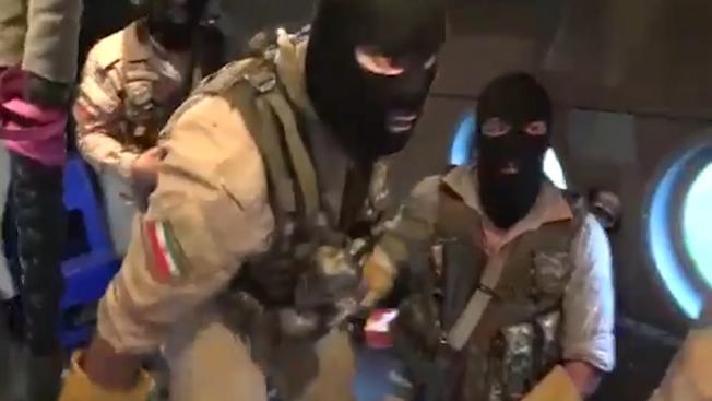 戴著滑雪面罩的伊朗突擊隊員,在直升機上準備行動。(Getty Images)
