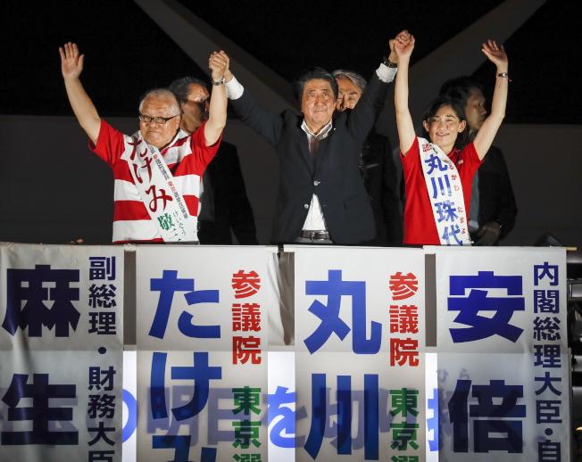 日本參議院21日舉行改選,首相安倍晉三按慣例在秋葉原舉辦選前之夜,支持者從下午就開始聚集;晚間安倍(中)登上宣傳車演說,與候選人一同振臂高呼。( 歐新社)