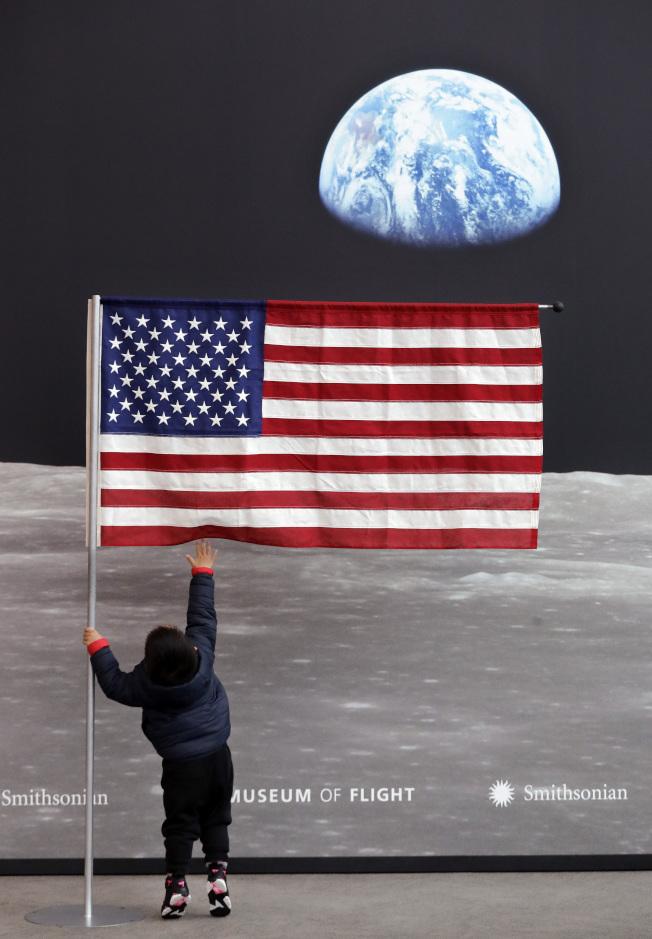 西雅圖舉行阿波羅登月特展,一名兩歲華童踮起腳來,觸摸進口處的美國國旗。(美聯社)