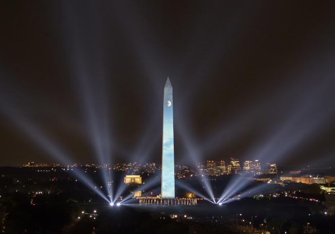 紀念阿波羅登月50周年,華府國家大草坪舉行燈光秀,把月球投影到華盛頓紀念碑上。(歐新社)