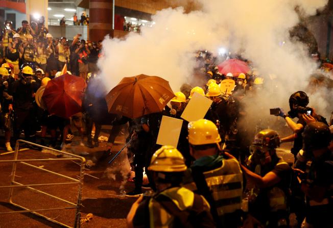 示威民眾21日晚間衝擊中共中央駐港聯絡辦公室後,港警晚間10點半後全力清場,發射多枚催淚彈。(路透)