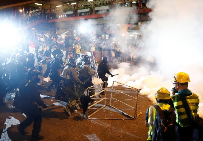示威民眾21日晚間衝擊中共中央駐港聯絡辦公室後,港警晚間10點半後全力清場,發射多枚催淚彈。但示威群眾退散後又重新集結與警方對峙。(路透)