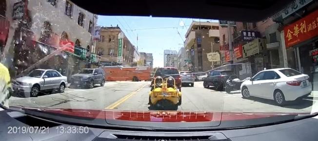 被嫌犯打破前面擋風玻璃的紅色汽車,車裡錄像機拍到嫌犯(左面)打玻璃的情形,打見一支長棍。(讀者提供)