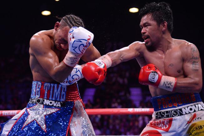 面對小自己10歲的不敗拳王瑟曼(左),40歲的菲律賓帕奎奧(右)第1回合就把瑟曼擊倒在地,雙方接著激戰打滿12回合,帕奎奧獲裁定獲勝,保住WBA世界次中量級拳王頭銜。(路透)