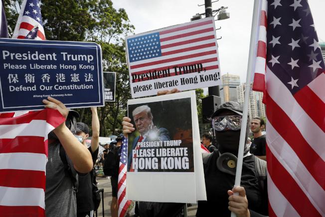 有的示威抗議者21日手上的標語是要「川普總統保衛香港」。 (美聯社)