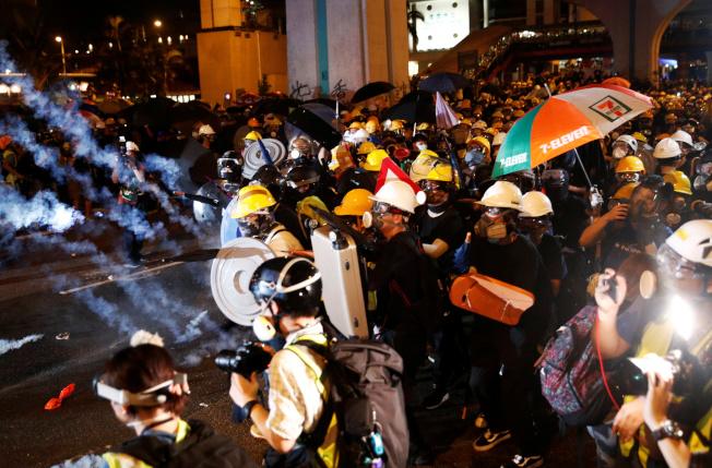 戴了面具口罩的反送中示威都21日晚在香港中聯辦大樓外,築起障礙物,與港警一戰。(Getty Images)