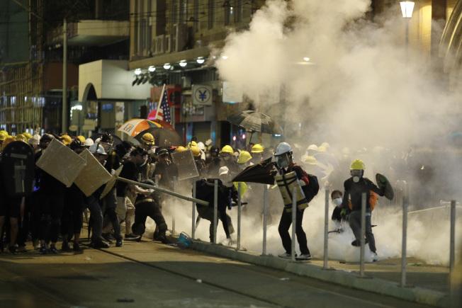香港警察21日晚10時半以後清場,發射多枚催淚彈,驅散示威者。(美聯社)