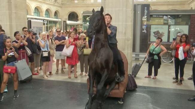 法國巴黎某個火車站,21日出現「馬上」藝術快閃演出,兩名演出者坐在馬背上,在車站與站內餐廳走動,表演特技,給乘客意外驚喜。路透