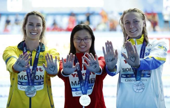 瑪姬.麥克尼爾(中)贏得女子蝶式百米金牌,並擊敗銀牌得主Sarah Sjostrom(右)所保持的世界紀錄,三名女將在領獎時伸出手掌,為正在抗癌的日本游泳好手Ikee打氣。(路透)