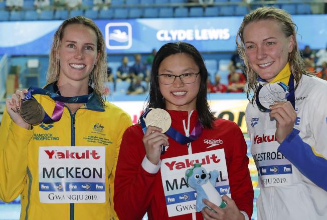 密西根大學華裔游泳選手麥克尼爾(中)22日在南韓破女子百米蝶式世界紀錄獲金牌,右為獲銀牌的瑞典選手Sarah Sjostrom,與銅牌的澳大利亞選手Emma McKeon 。 (美聯社)