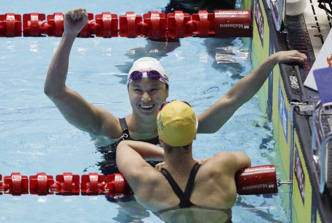 密西根大學華裔游泳選手麥克尼爾 22日在南韓破 女子百米蝶式世界紀錄後,高興舉起手   臂。 (美聯社)