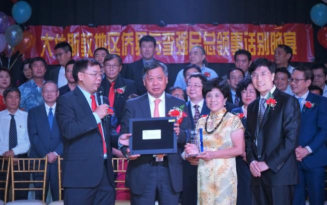 中國人活動中心董事長靳敏(右一)、執行長範玉新(左一)代表僑界向李強民(左二、三)伉儷贈送電子圖片集。(記者賈忠/攝影)