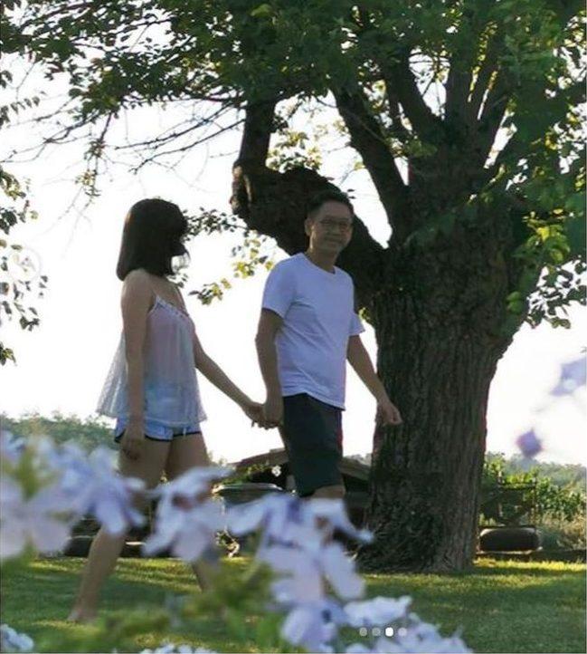 李嘉欣和老公穿白色情侶裝,在樹下手牽手漫步。(取材自Instagram)