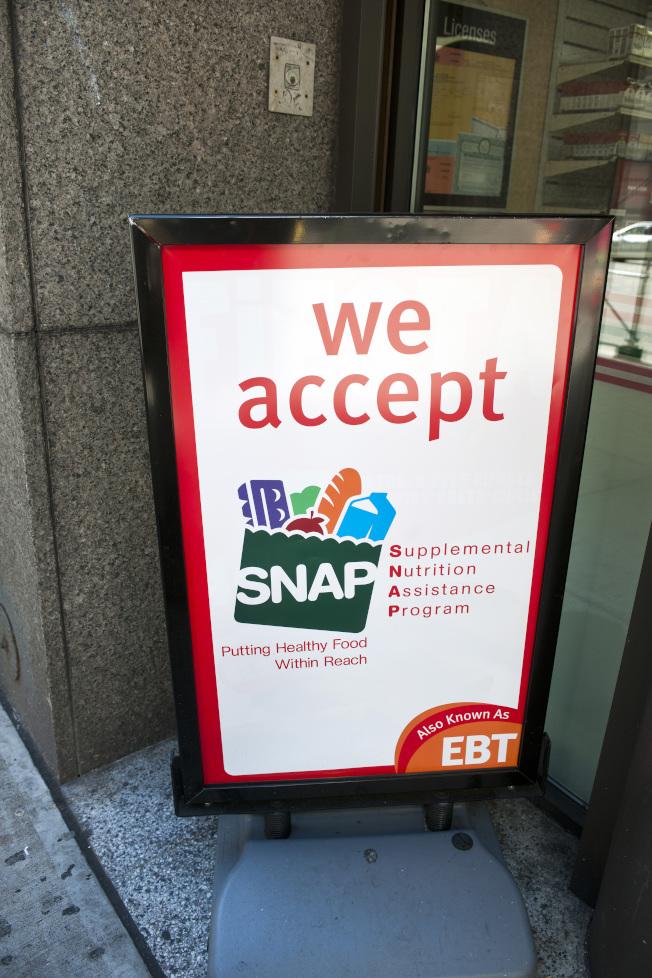 川普政府將緊縮糧食券規定,圖為一家商店門口掛出招牌,接受糧食券。(美聯社)