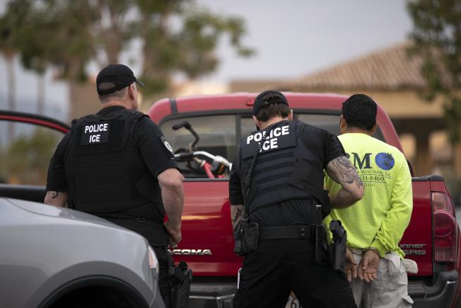 移民暨海關執法局7月8日在加州逮捕一名無證移民,為他戴上手銬。(美聯社)