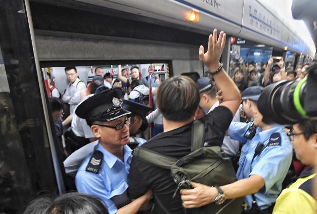 10多名著黑衣的反送中示威者24日早上響應號召,在港島地鐵金鐘站阻礙列車行走,造成港島線地鐵一度被癱瘓延誤10至15分鐘。(中通社)